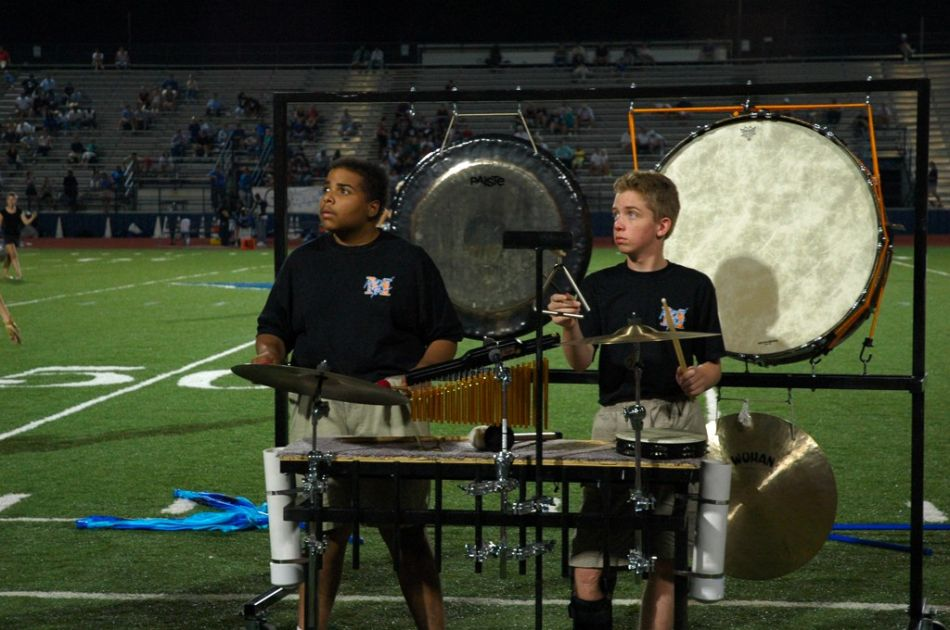 Playing the triangle and cymbal, he also plays the chimes, tamborine, and the bass drum, gong, and cymbal you see behind him